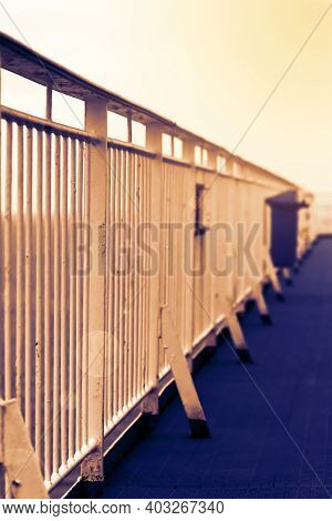 Handrails On The Promenade Deck Of A Large Cruise Ship In Warm Sunset Lighting. Blurred Out Backgrou