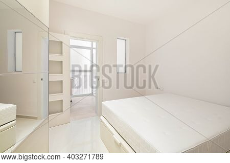 White Bedroom With Bed, Wardrobe And Entrance To Bathroom In A Modern Refurbished Apartment Ready To