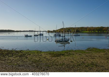 Boats Moored At Dell Quay In Chichester Harbour, West Sussex, England. With Clear Blue Sky And Flat