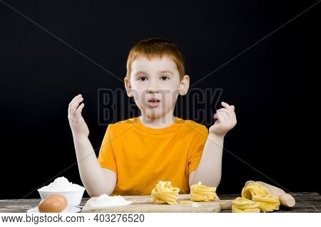 Portrait Of A Baby Boy In The Kitchen While Helping To Prepare Food, A Boy With Red Hair And Beautif