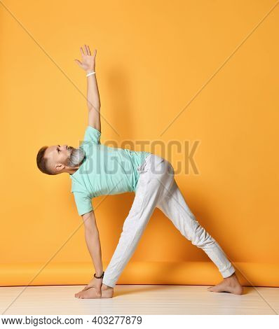 Mature Handsome Bearded Gray-haired Man In Sportswear Practicing Yoga, Standing In The Pose Of An El