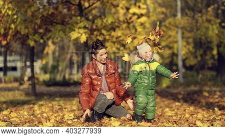 Mom And Son Throw Autumn Leaves In Autumn Park, Family Fun. Family Enjoying A Walk In Nature. Happy