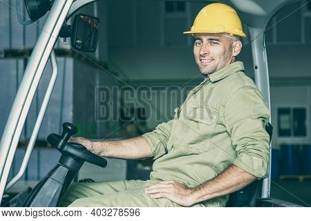 Portrait Of Happy Male Warehouse Worker In Hardhat Driving Forklift In Warehouse, Holding Steering W