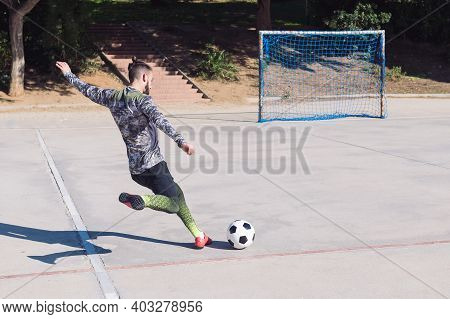 Rear View Of A Football Player Kicking The Soccer Ball Into An Empty Goal In A Concrete Football Cou