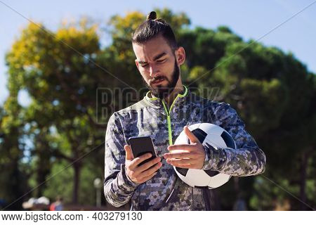 Fashionable Sportsman With A Soccer Ball Consulting His Mobile Phone With Confused Expression Due To