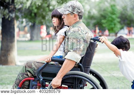 Disabled Military Veteran Walking With Two Children In Park. Girl Sitting On Dads Lap, Boy Pushing W