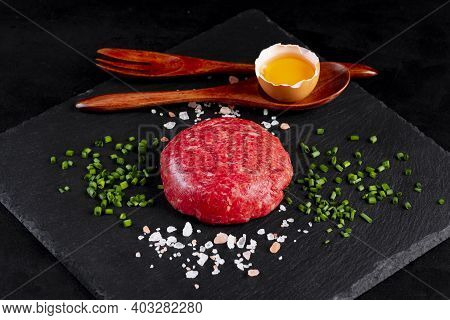 Beef Tartar With Egg Served On A Black Stone Plate. Tartar On A Black Plate With Herbs, Salt And Chi