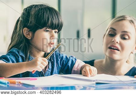 Pensive Young Female Teacher Helping Primary School Girl To Do Her Task. Little Girl Pointing At Her