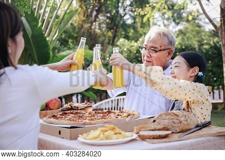 Happy Asian Family Having Enjoying Meal(pizza, Salad,snack, Orange Juice) Together And Cheers Of Ora