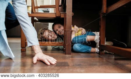 Two Little Kids Siblings Playing Hide And Seek Game With Grandfather At Home, Hiding Under The Chair