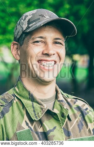 Cheerful Man In Military Camouflage Uniform Standing In Park, Looking At Camera And Smiling. Green T