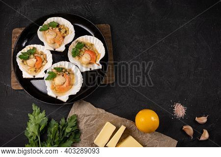 Scallops, Lemon, Garlic, Parsley, Butter And Salt On Black Background. Baked Scallops With Caviar An