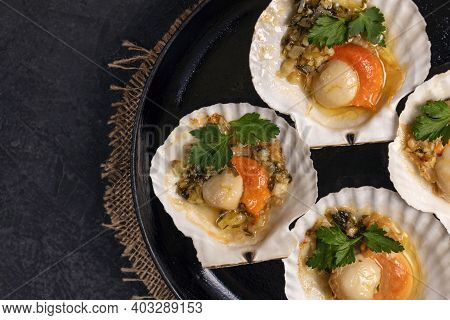 Scallops, Lemon, Garlic, Parsley, Butter And Salt On Black Background. Close Up Baked Scallops With