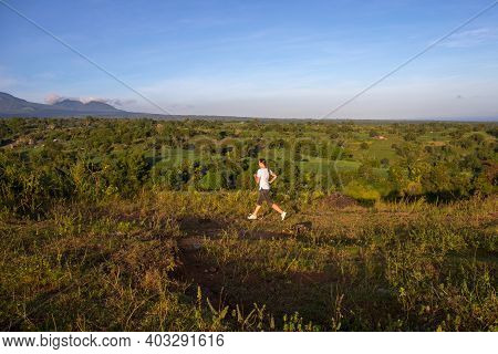Young Woman Running In Natural Environment. Tropical Island Landscape In Golden Hour. Summer Vacatio