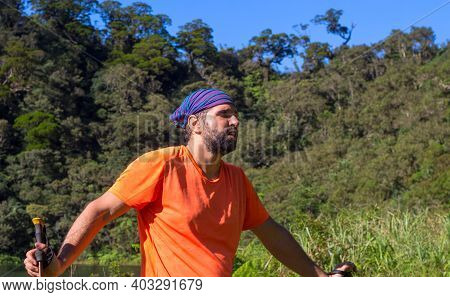 Tired Trekker On Forest Landscape Background. Wild Nature View With Male Tourist. Man In Treking Or