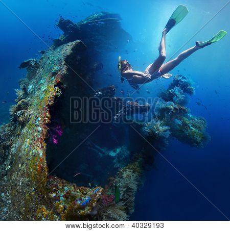Underwater shoot of a woman exploring USAT Liberty wreck on a breath hold. Tulamben, Bali island, Indonesia