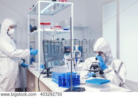 Close Up Of Scientist Using A Microscope A Microscope Wearing Ppe Suit In Equipped Lab. Chemist Rese