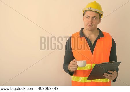 Studio Shot Of Young Muscular Man Construction Worker Thinking While Holding Clipboard And Coffee Cu