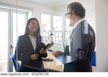 Happy Young Businesswoman Talking With Confident Grey-haired Ceo. Successful Content Pretty Secretar