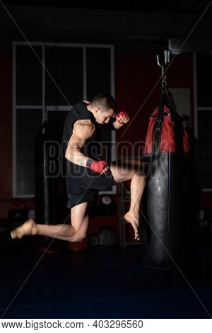 Kickboxing Fighter Performing Jumping Air Kicks With Knee On Punch Bag. Caucasian Man Practicing Mar