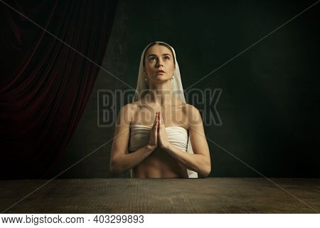 Praying. Modern Remake Of Classical Artwork - Young Medieval Woman In White Cloth On Dark Studio Bac