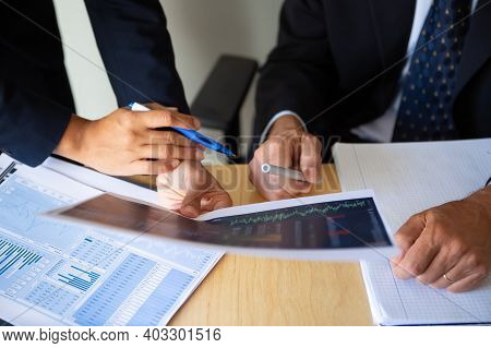 Investor And Broker Discussing Trading Strategy, Holding Papers With Financial Charts And Pens. Crop