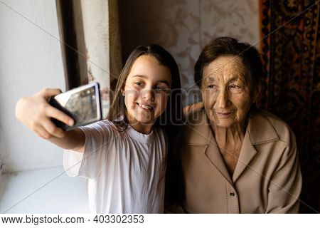 Great-grandmother Sits With Great-granddaughter And Looks Into The Smartphone. Grandmother And Child