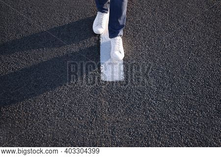 Man Walking Along White Line On Road, Closeup With Space For Text. Way Concept