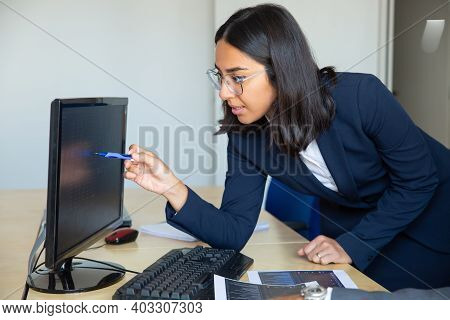 Focused Female Professional Pointing Pen At Statistic Report On Monitor, Leaning On Office Table Wit
