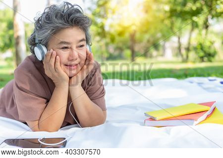 Senior Happy Woman Listening Music At Park By Wear Headphone And Using Digital Tablet Elderly Woman