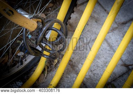 Black Bicycle Safety Locker And Wheel On A Yellow Pole Of A Bike Parking. Stolen Bike