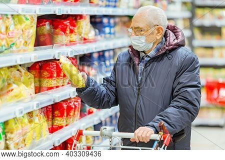 Old Senior European Man Wearing Protective Facial Mask Looking At Groceries In The Supermarket. Shop