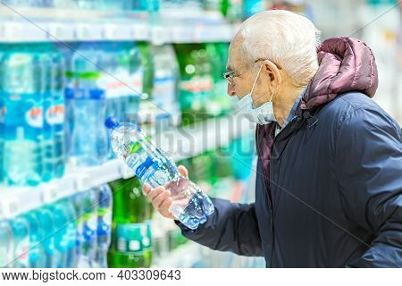 Old Senior European Man Wearing Protective Facial Mask Looking At Mineral Water Bottle In The Superm