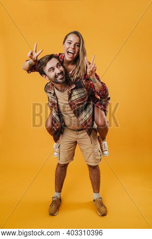 Young happy couple playing together piggyback isolated on yellow background, full length