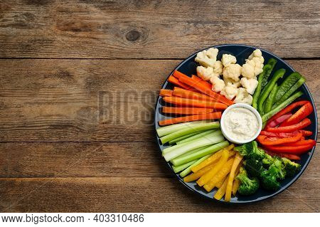 Plate With Celery Sticks, Other Vegetables And Dip Sauce On Wooden Table, Top View. Space For Text
