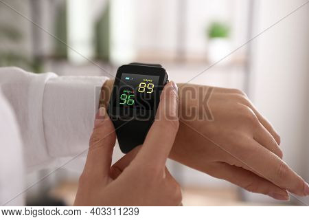 Woman Measuring Oxygen Level With Smartwatch Indoors, Closeup