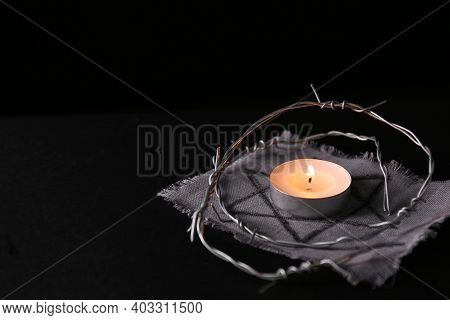 Fabric With Star Of David, Barbed Wire And Burning Candle On Black Background, Space For Text. Holoc