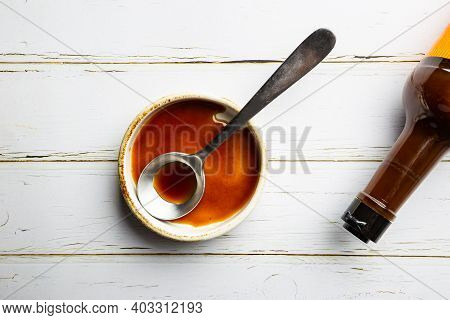 Worcestershire Sauce In A Bowl With Spoon And Bottle Over White Background, Top View