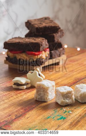 Desserts On Top Of A Wood Table, With Marble Background And Lights. Brownies, Cookies, Italian Fudge