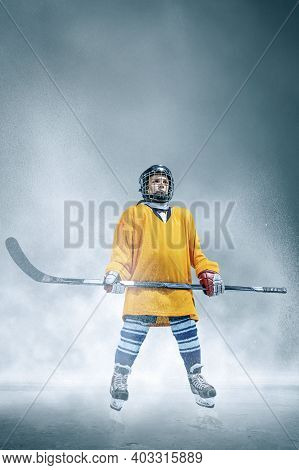 Champion. Little Hockey Player With The Stick On Ice Court And Smoke Background. Sportsboy Wearing E