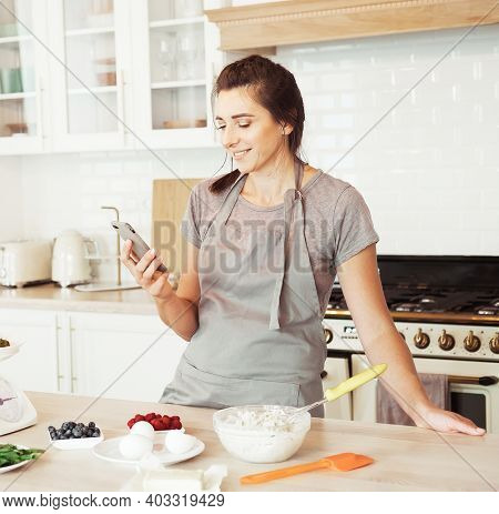 Lifestyle, cooking and freelance concept: Image of smiling brunette woman wearing apron using cellphone while cooking pie in modern kitchen