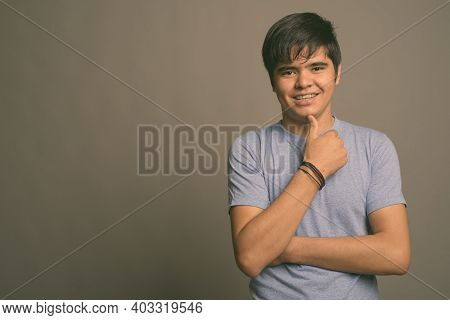 Young Asian Teenage Boy Wearing Blue Shirt Against Gray Background