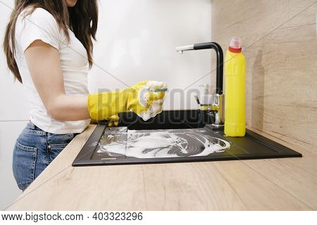 Cleaning The Kitchen In Protective Gloves.close-up Of A Woman Cleaning A Kitchen At Home