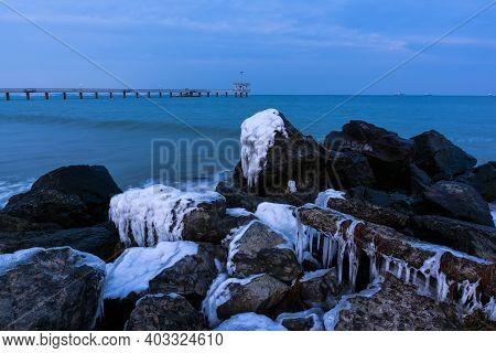 Winter Black Sea Landscape From Burgas Bay, Bulgaria. Blue Hour Sunset. Frozen Rocks And Bridge.