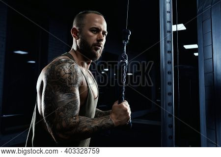 Portrait Of Muscular Tattooed Bodybuilder Doing Crossover Exercise. Side Close Up Of Bearded Man Wit