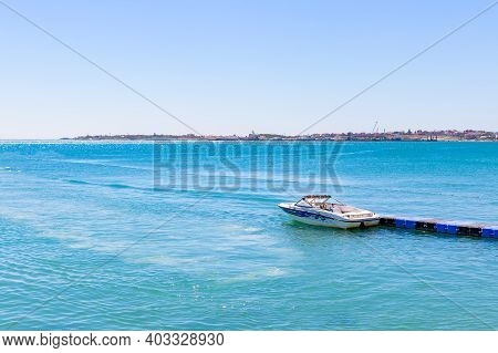Gelendzhik, Russian Federation - August 17, 2020: White Boat Is Moored Against Bright Blue Sea On Su