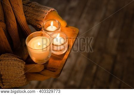 Cropped View Of Woman In Knitwear And Gloves Holding Burning Candles On Wooden Board