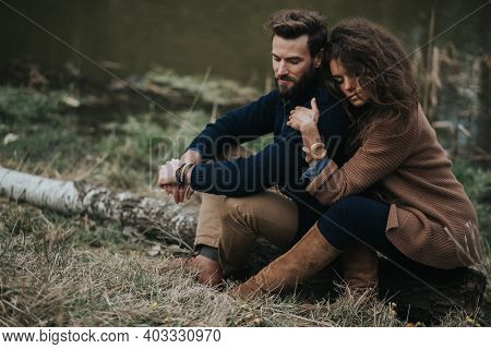Happy Caucasian Lovers Are Sitting On The Shore Of The Lake. Young Couple Is Hugging On Autumn Day O
