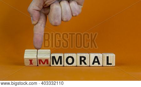 Moral Or Immoral Symbol. Hand Turns Cubes And Changes The Word 'immoral' To 'moral'. Beautiful Orang