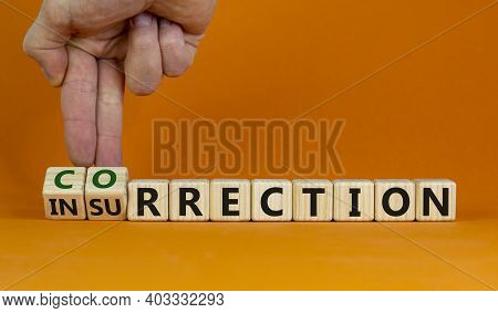 Correction Vs Insurrection Symbol. Businessman Turns Wooden Cubes And Changes Word Insurrection To C